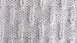 Caterpillar Knit Stitch Pattern in white yarn on knitting needle.
