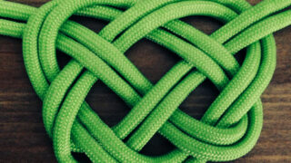 Celtic Heart Knot with double strands of green colored rope atop wooden background.
