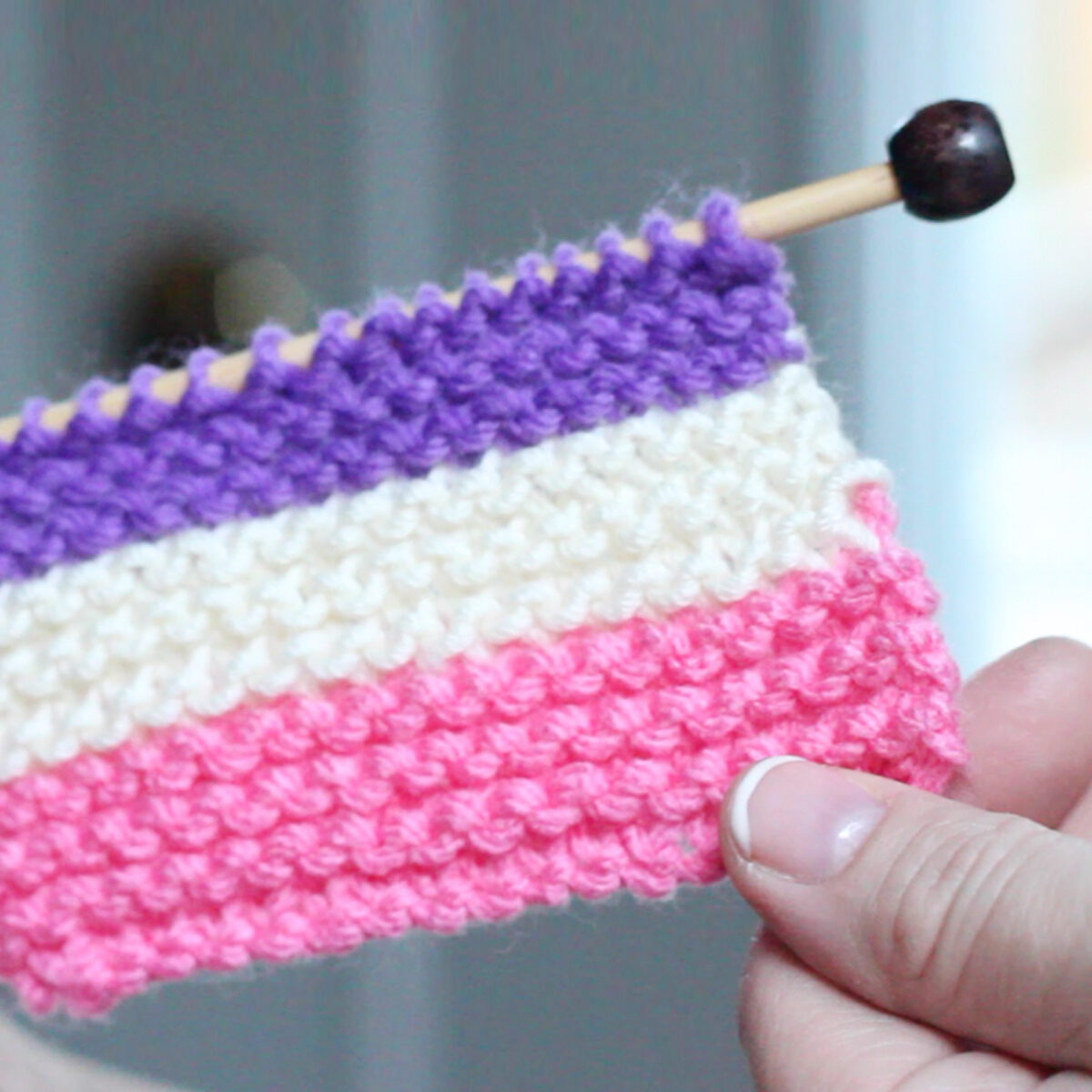 Knitted Swatch of horizontal stripes in purple, white, and pink color yarn on knitting needle with hands holding.