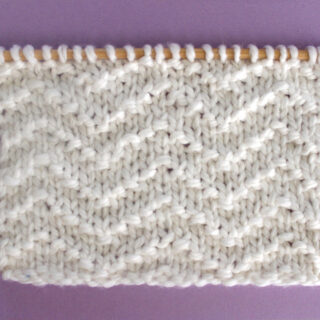 Chevron Seed Knit Stitch Pattern texture in white color yarn on knitting needle.
