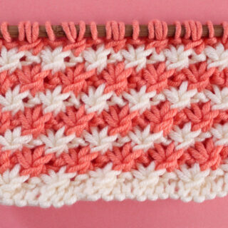 Daisy Stitch Knitting Pattern texture in alternating orange and white colors of yarn on knitting needle.
