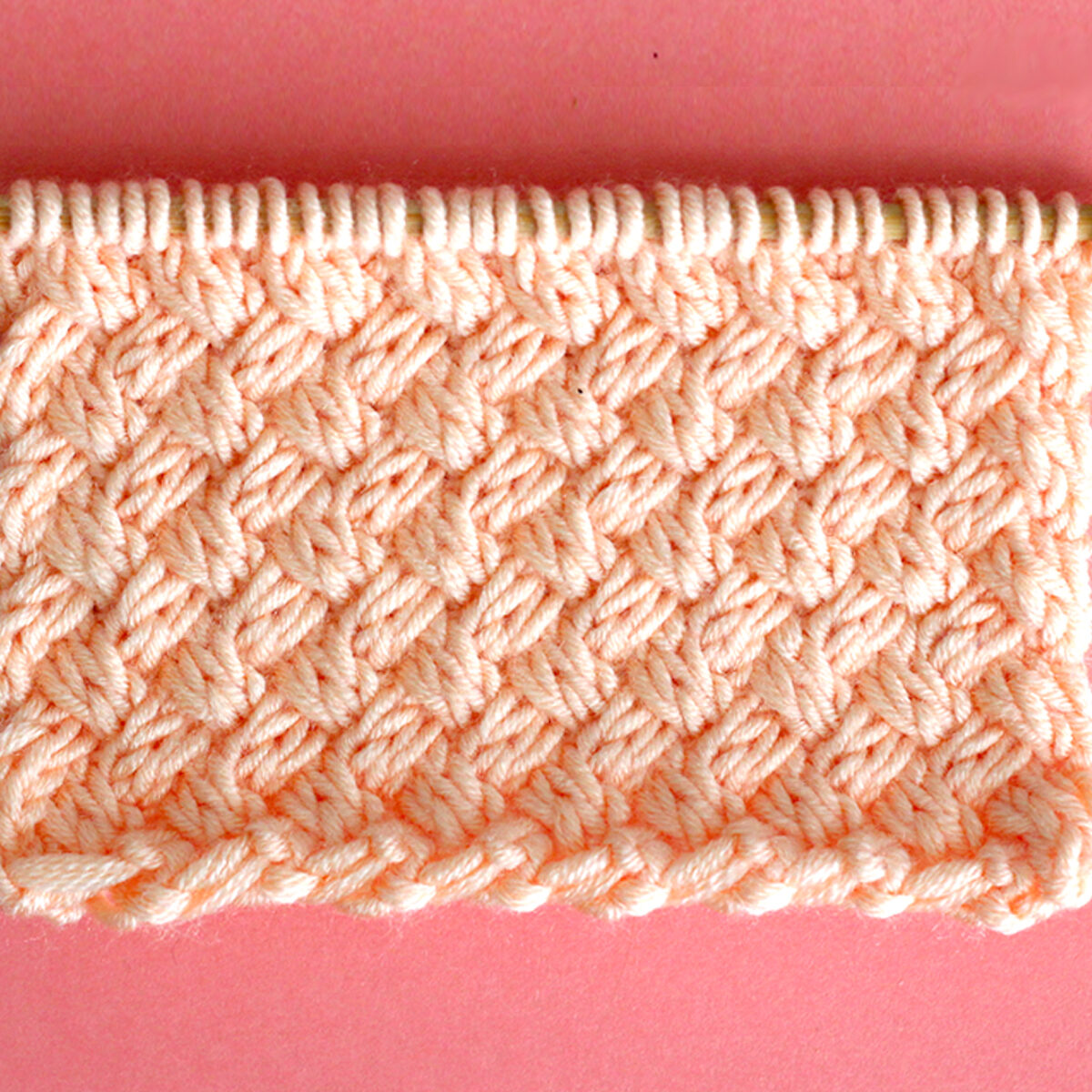 Diagonal Basket Weave Cable Knit Stitch Pattern texture in peach color yarn on knitting needle.