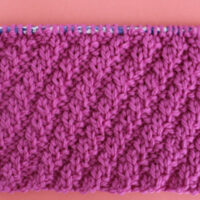 Diagonal Rib Cable Knit Stitch Pattern texture in pink color yarn on knitting needle.