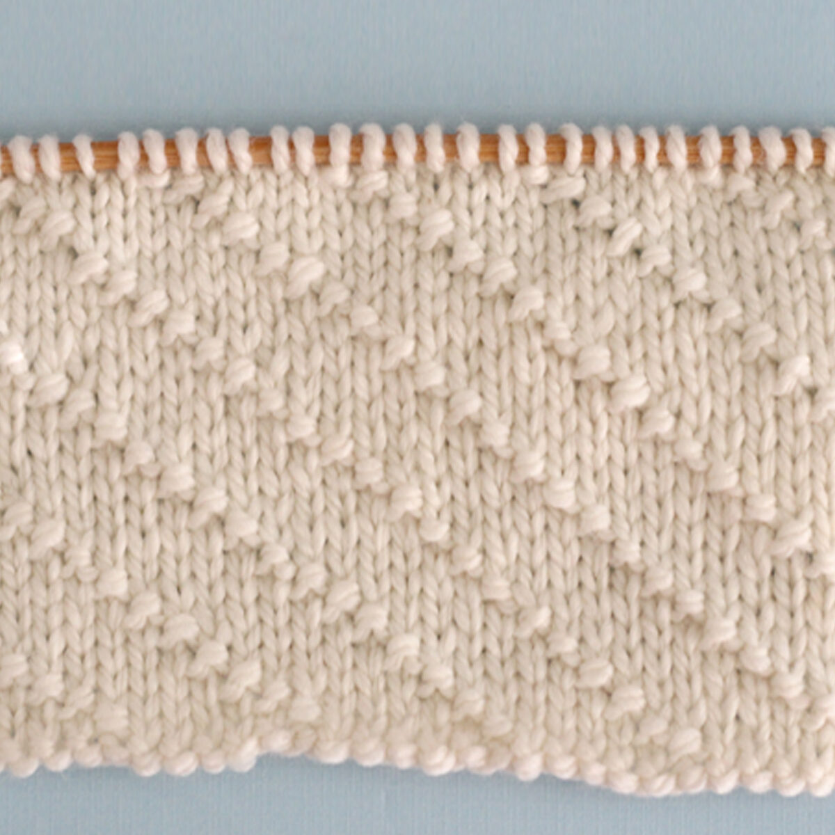 Diagonal Seed Knit Stitch Pattern in white yarn on knitting needle.