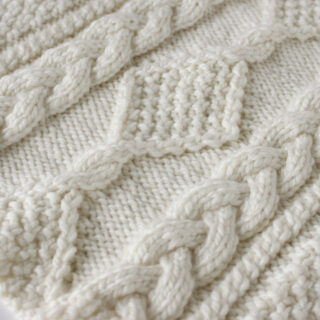 Celtic Cable Knitting Pattern swatch in white yarn.
