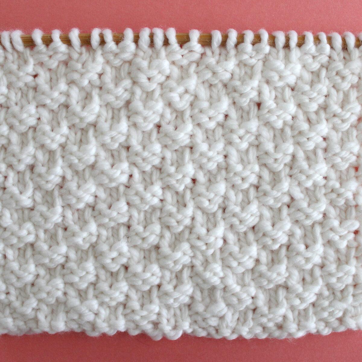 Double Moss Knit Stitch Pattern in white yarn on knitting needle.
