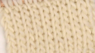 Double Stockinette Knit Stitch Pattern in white color yarn on knitting needle.