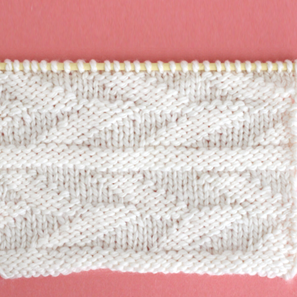 Knitted Embossed Leaf Stitch Pattern in white yarn on knitting needle.