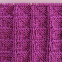 Knitted Flag Stitch Pattern in purple yarn on knitting needle.