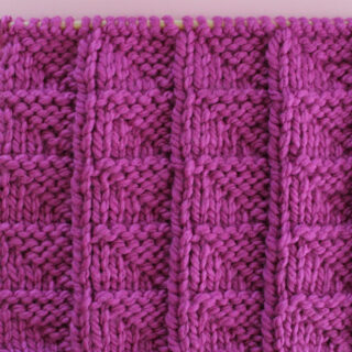 Knitted Flag Stitch Pattern in purple yarn on knitting needle.