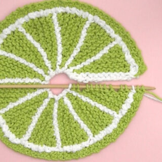 Knitted fruit slice shape in green color yarn atop a pink background.