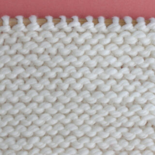Garter Knit Stitch Pattern with white yarn color on a knitting needle.