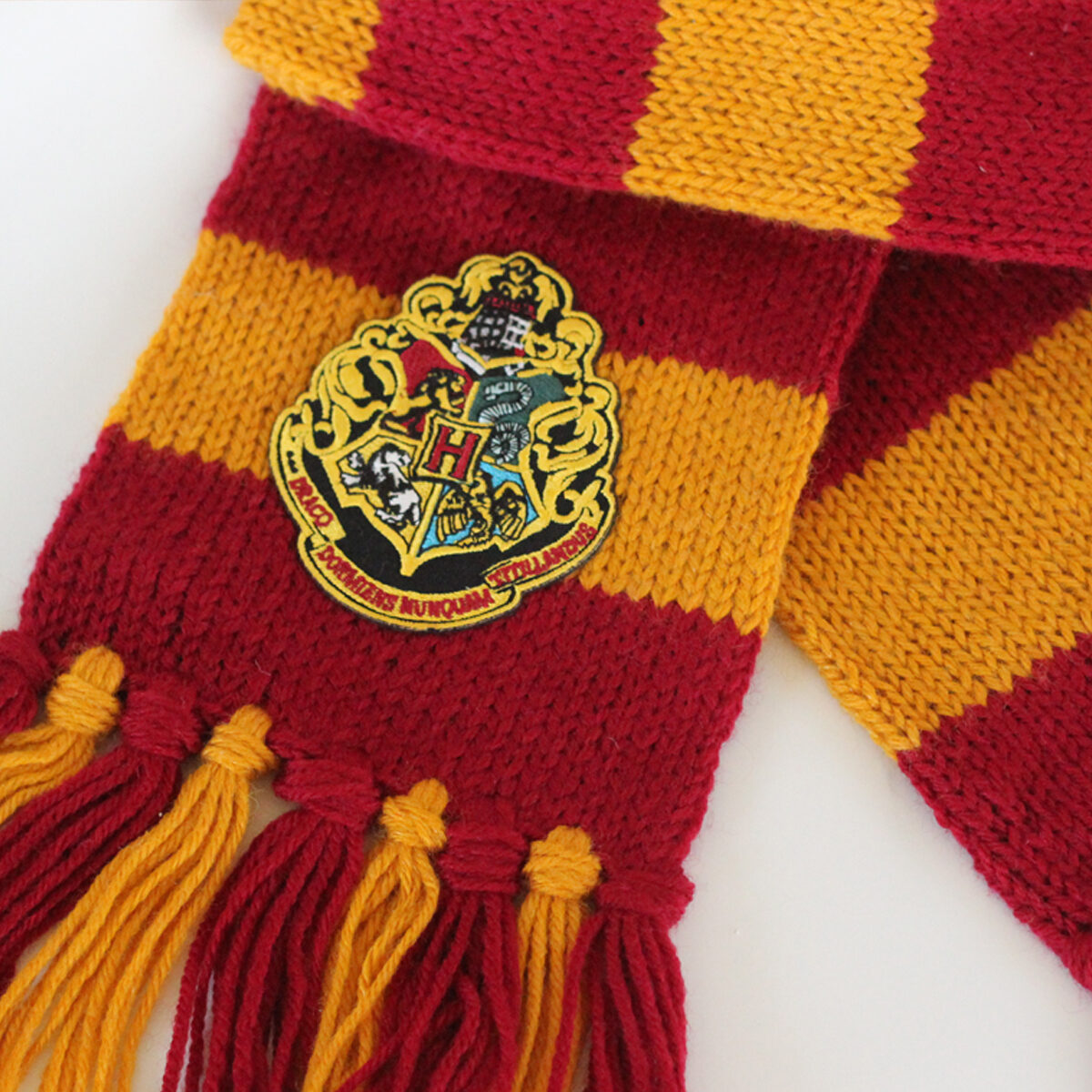 Harry Potter Knitted Scarf in Burgundy and Gold yarn colors with Hogwarts patch.