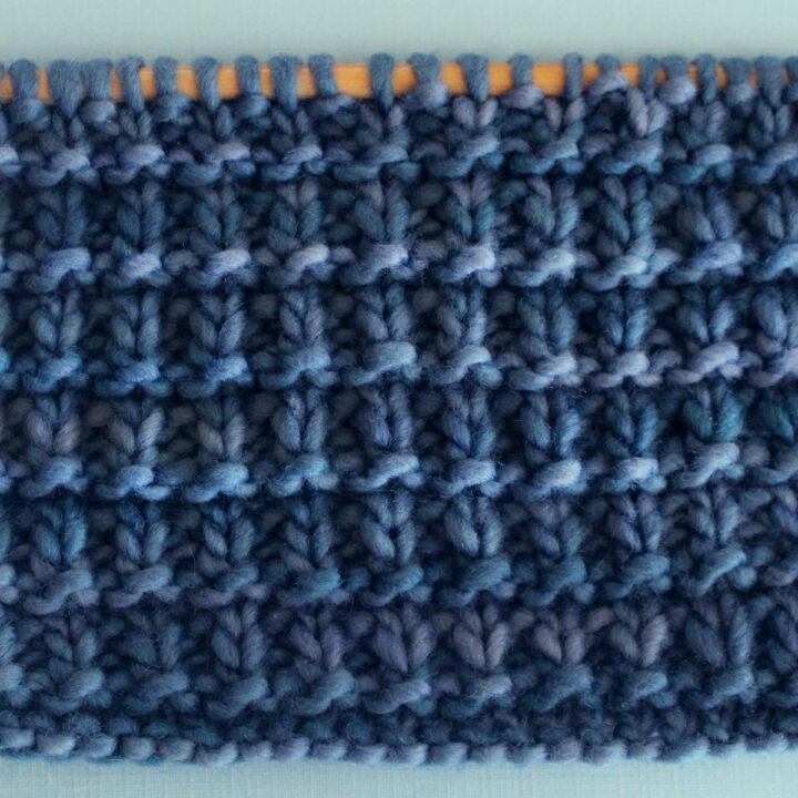 Hurdle Basket Weave Stitch Knitting Pattern in blue yarn color on knitting needle.