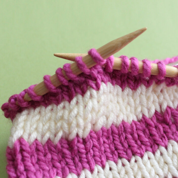 Knitted sample in horizontal stripes in pink and white yarn color on circular knitting needles.