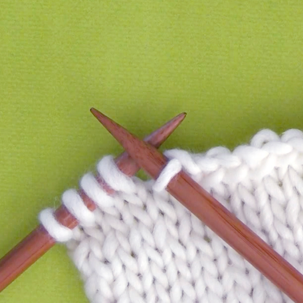 Knitted swatch of white yarn in stockinette stitch pattern with two wooden knitting needles.