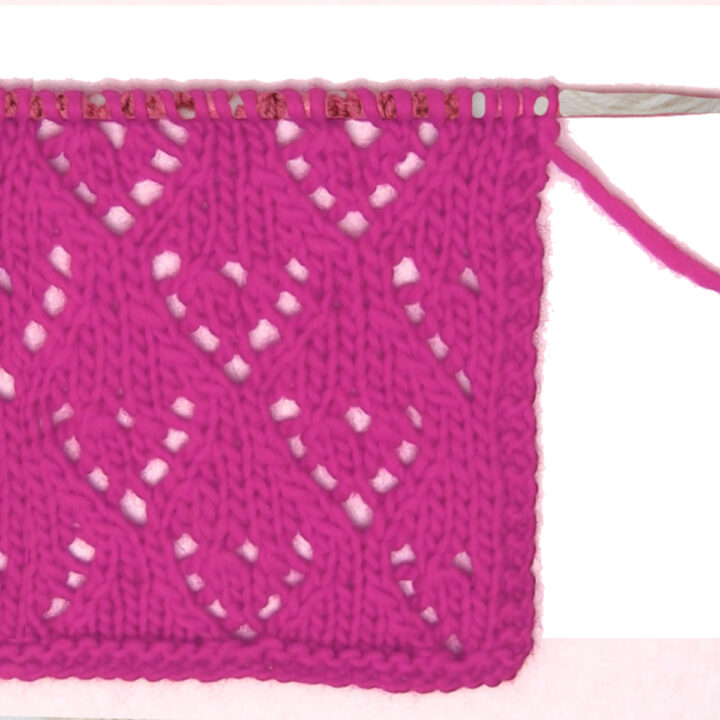 Mini Lace Heart Knit Stitch Pattern in pink yarn on knitting needle.