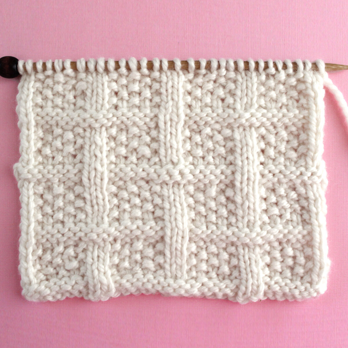 Lattice Seed Knit Stitch Pattern texture in white color yarn on knitting needle atop a pink background.