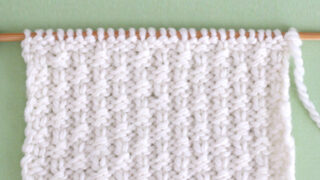 Little Raindrops Knit Stitch Pattern in white yarn on knitting needle atop a green background.