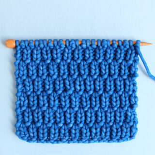 Long Raindrops Knit Stitch Pattern in bright blue yarn color on knitting needle atop a light blue background.