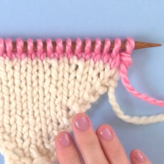 Make One Knitting Increase Sample in white and pink yarn with woman's hand