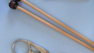 Two straight wooden bamboo knitting needles, a pair of stork shaped scissors, and a tapestry needle atop a blue background.