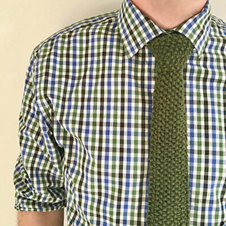 Knitted Necktie in seed stitch pattern with green yarn worn by a model in a checkered shirt.