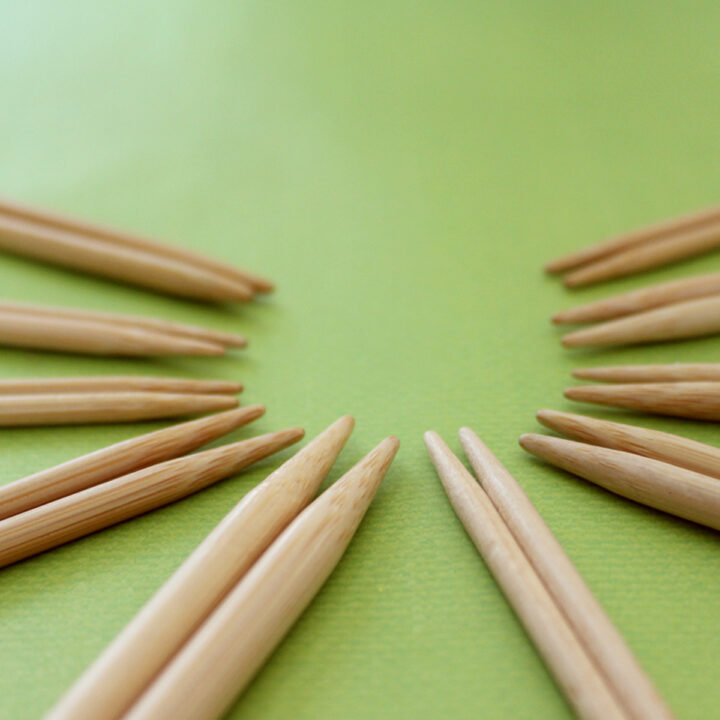 Ten pairs of wooden bamboo knitting needles arranged in a circular pattern atop a green background.