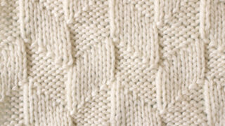 Parallelogram Knit Stitch Pattern texture in white yarn on knitting needle.