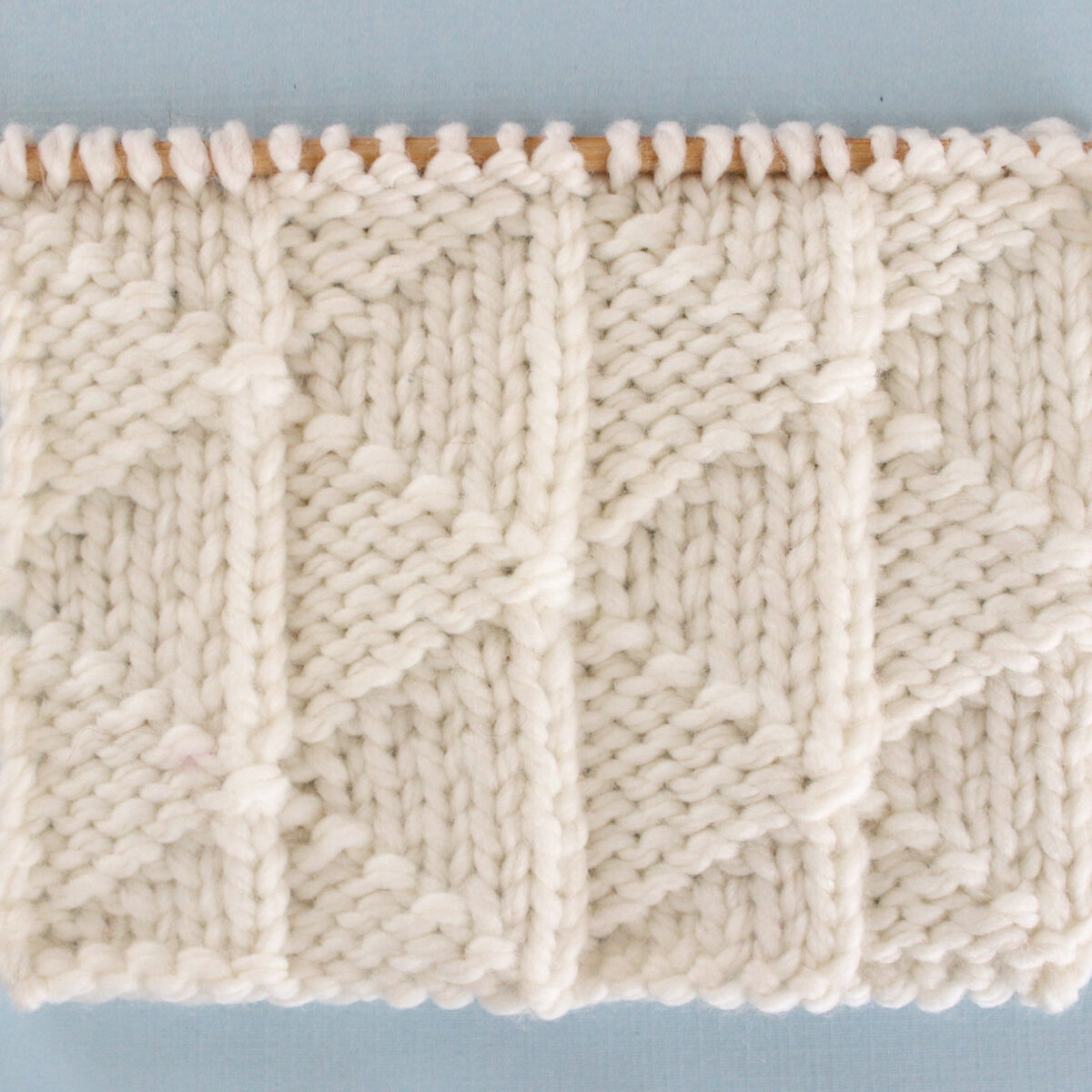 Pennant Pleating Knit Stitch Pattern in white yarn on knitting needle.