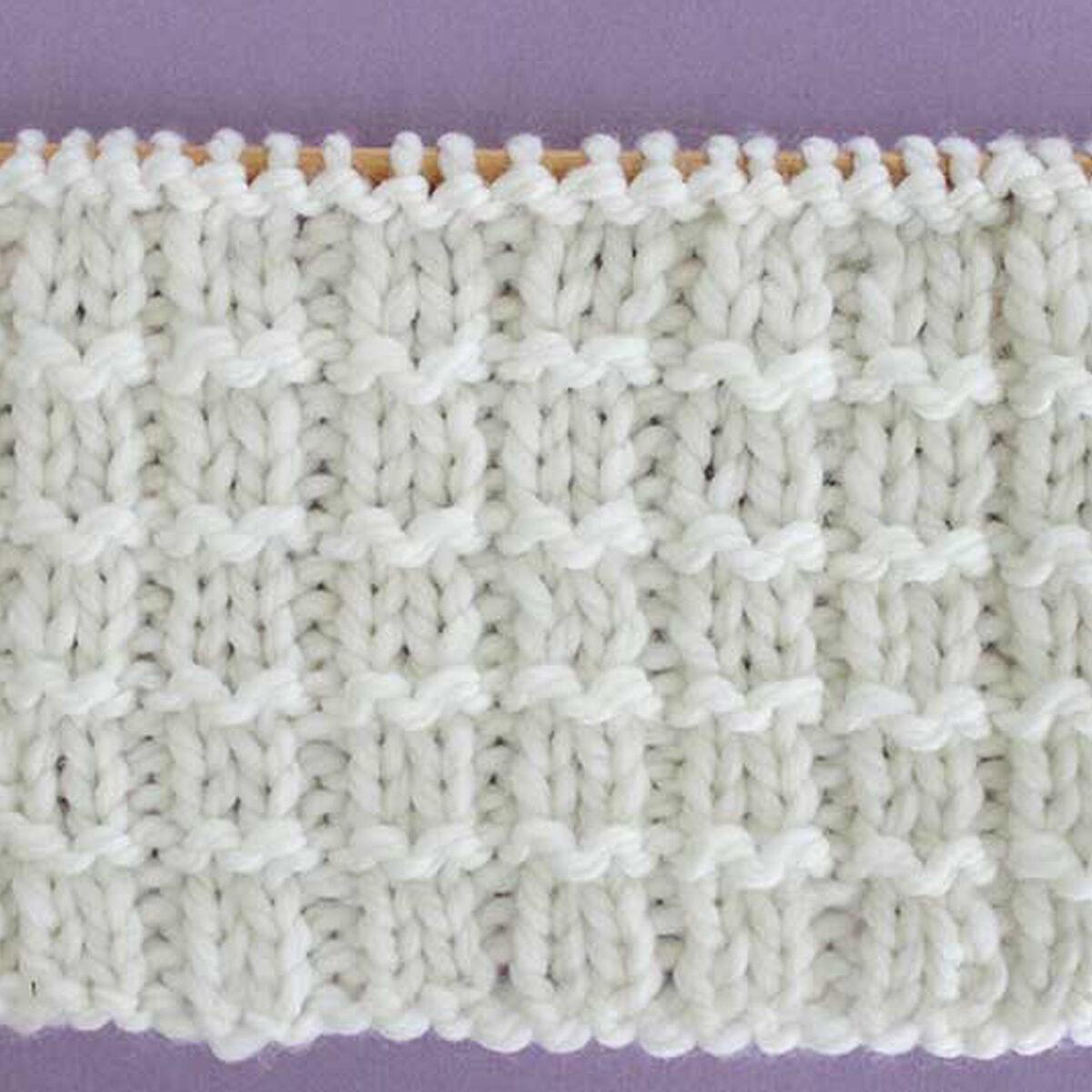 Pique Rib Knit Stitch Pattern in white yarn on knitting needle.