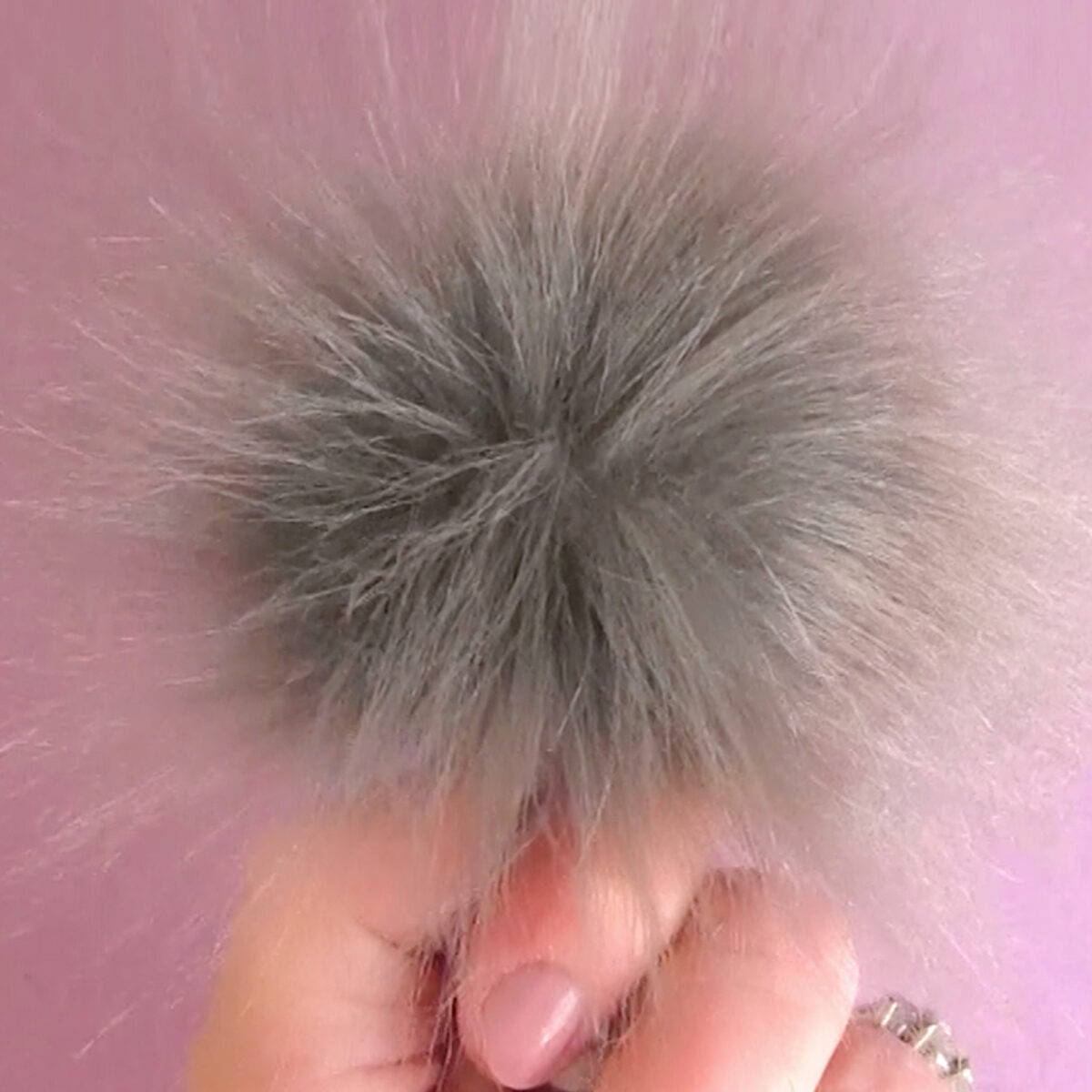 Pom Pom in Faux Fur Fabric in color grey held by hand.