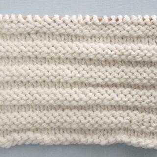 Knitted Reverse Ridge Stitch Pattern in white yarn on knitting needle.