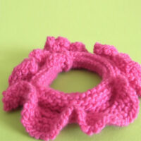 Knitted Hair Scrunchie in hot pink yarn color laying on a green background.