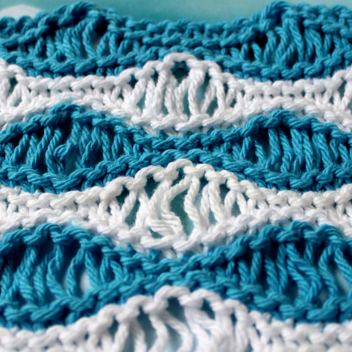 Knitted swatch in Sea Foam Wave pattern in horizontal stripes of blue and white color yarn.