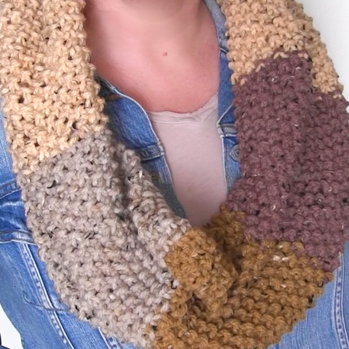 Knitted Seed Stitch Infinity Scarf in different shades of brown yarn colors worn by woman in jean jacket.