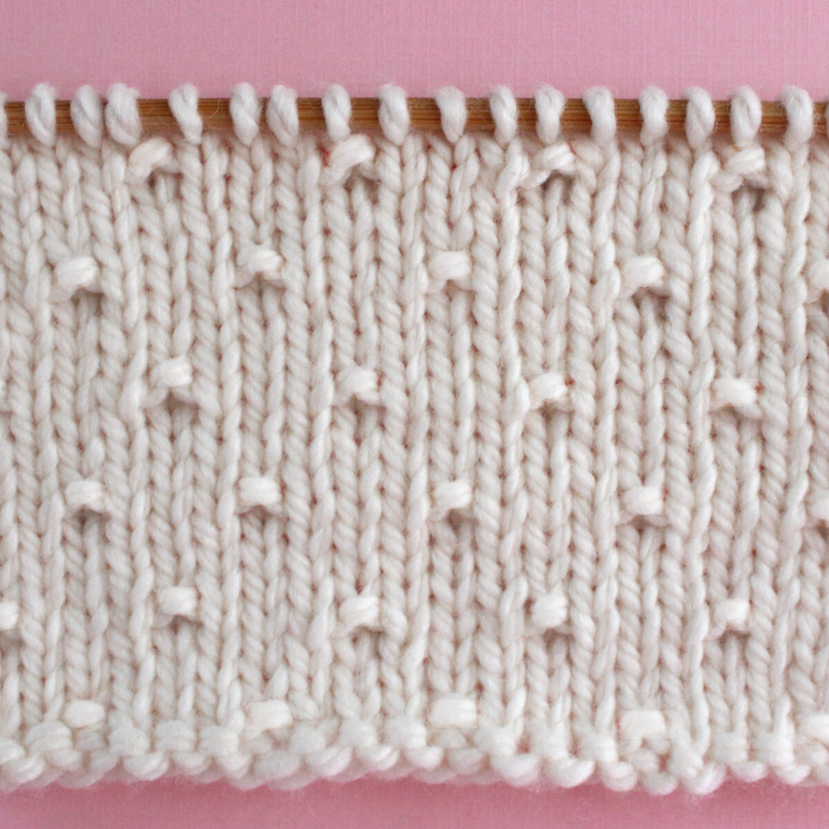 Simple Seed Knit Stitch Pattern in white yarn color on knitting needle.