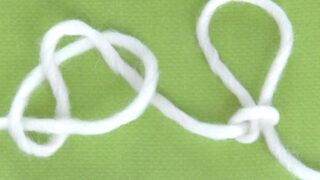 White yarn demonstrating the Slip Knot technique atop a green background.