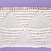 Knitted Stacked Triangle Stitch Pattern texture in white yarn on knitting needle.