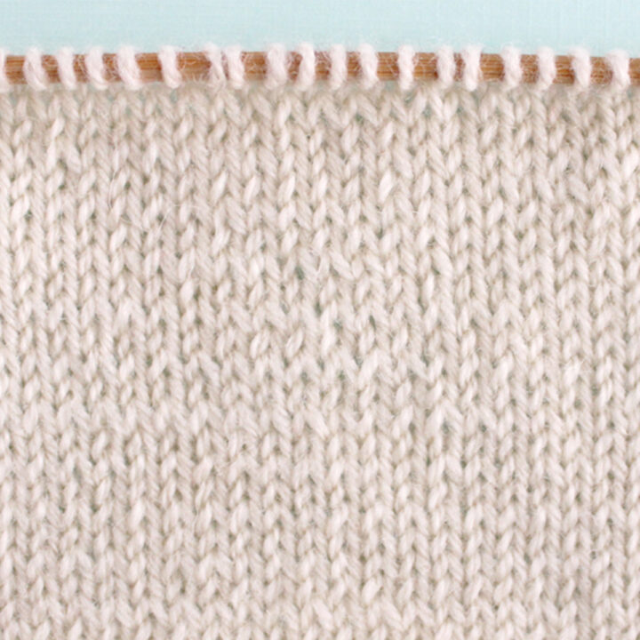 Stockinette Knit Stitch Pattern texture in white color yarn on knitting needle.