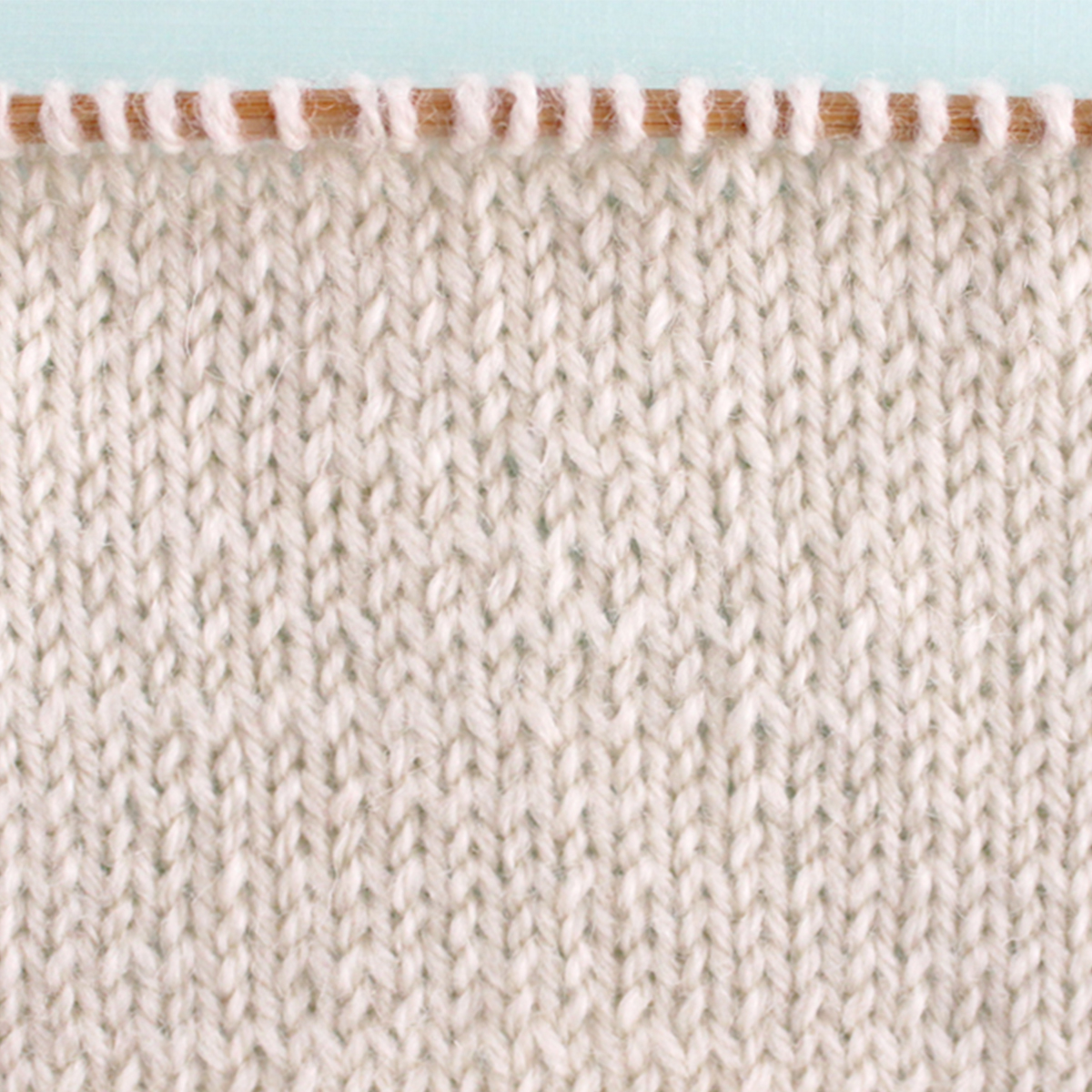 Stockinette pleteni uzorak uzorak tekstura u bijeloj boji pređe na igli za pletenje.