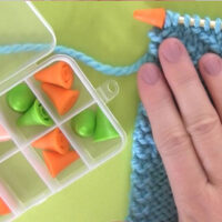 Needle Point Protector Stoppers on Knitting Needle with knitted swatch and hand.