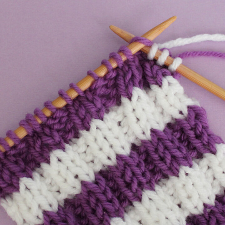 Knitted Stripes in rib stitch pattern with purple and white yarn colors on knitting needles.