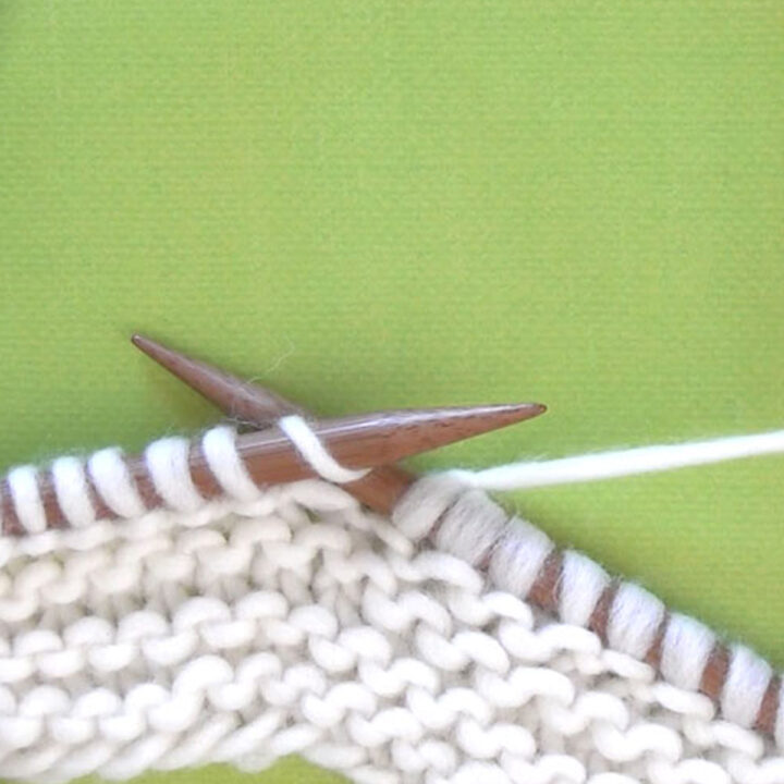 Two straight wooden bamboo knitting needles with a garter stitch sample in white yarn color atop a green background.