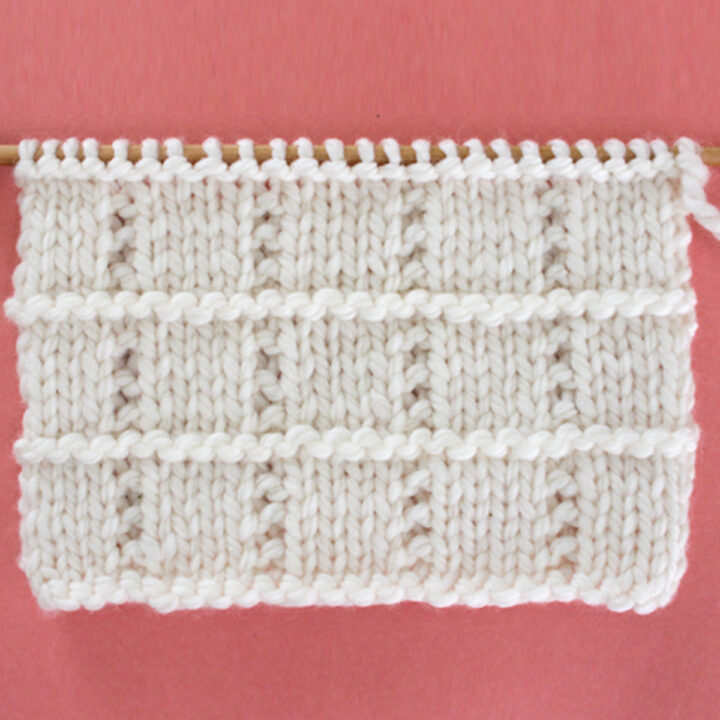 Tile Squares Knit Stitch Pattern in white yarn on knitting needle.