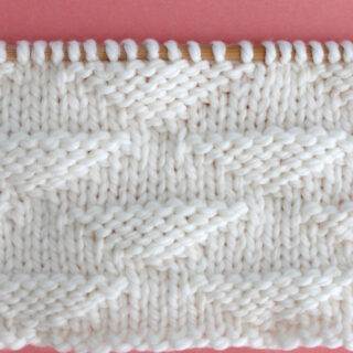 Pique Triangle Knit Stitch Pattern in white yarn on knitting needle.