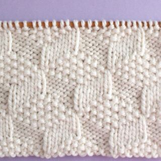 Tumbling Moss Knit Stitch Pattern in white yarn color on knitting needles.