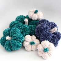Knitted Pumpkin Softies in blue, green, and white yarn colors with velvet yarn.