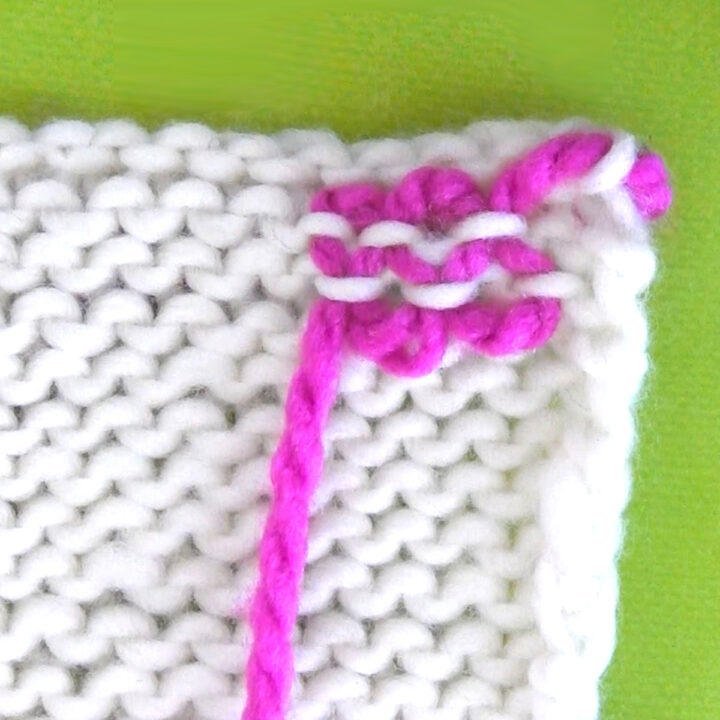 Yarn ends woven into a white knit swatch demonstrated by bright pink yarn.