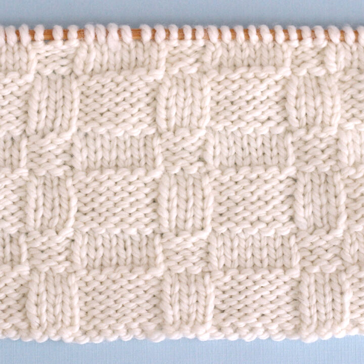Knitted Wide Basket Weave Stitch Pattern in white yarn on knitting needle.